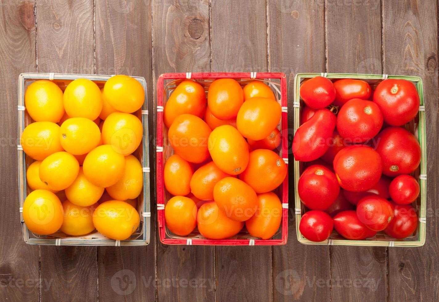 Colorful tomatoes on wooden table photo