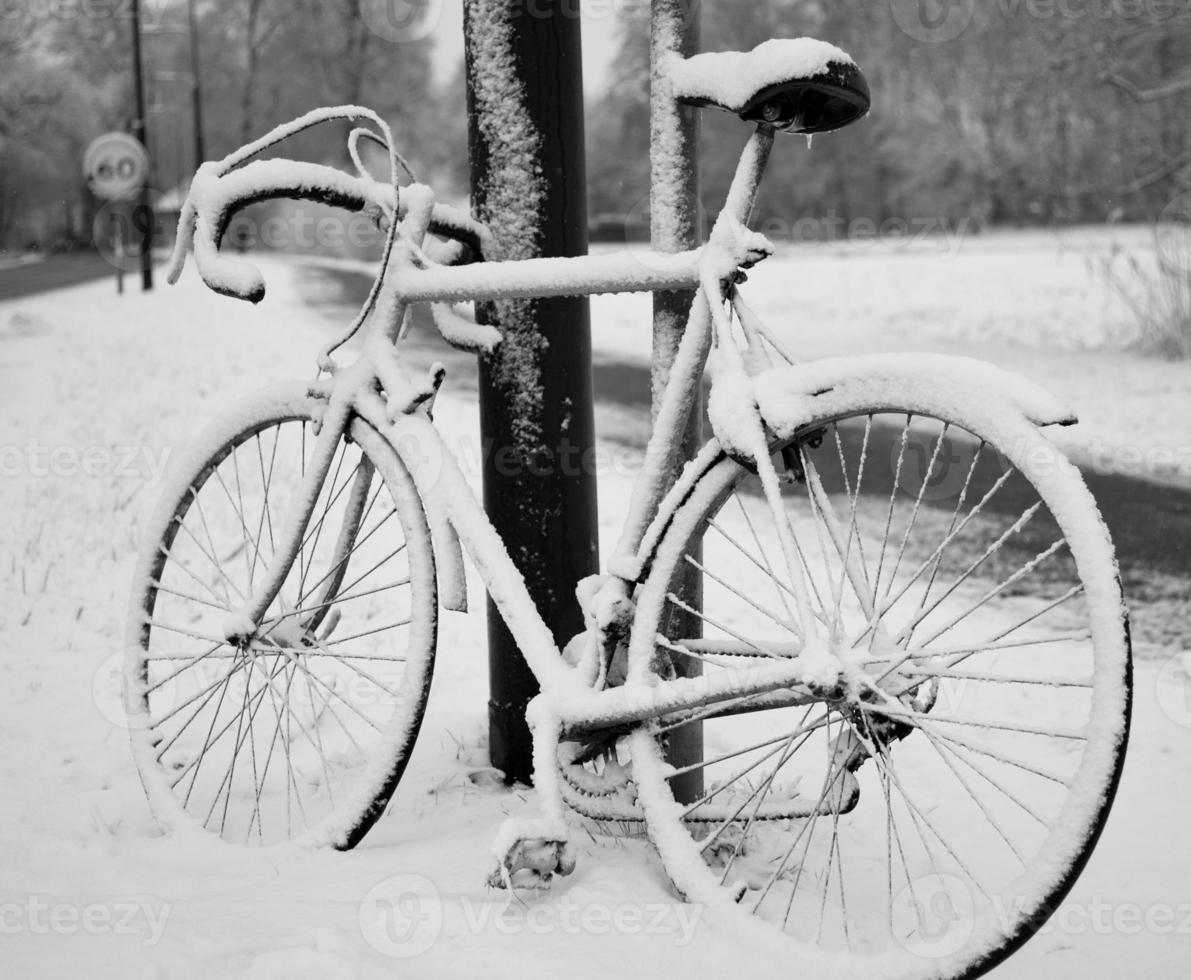 Black and white view of bike resting against pole in snow photo