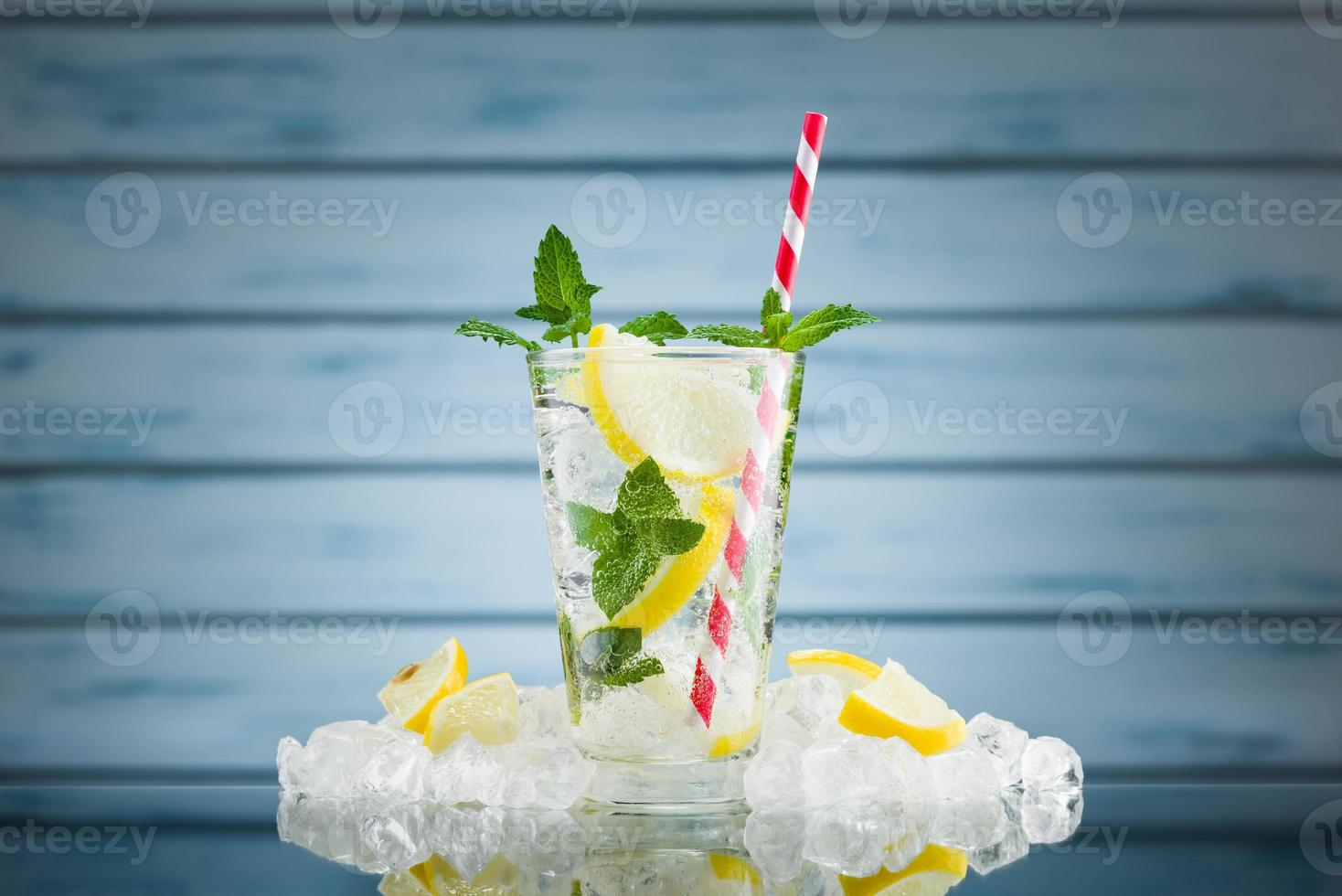 Lemon water in glass on blue wooden background photo