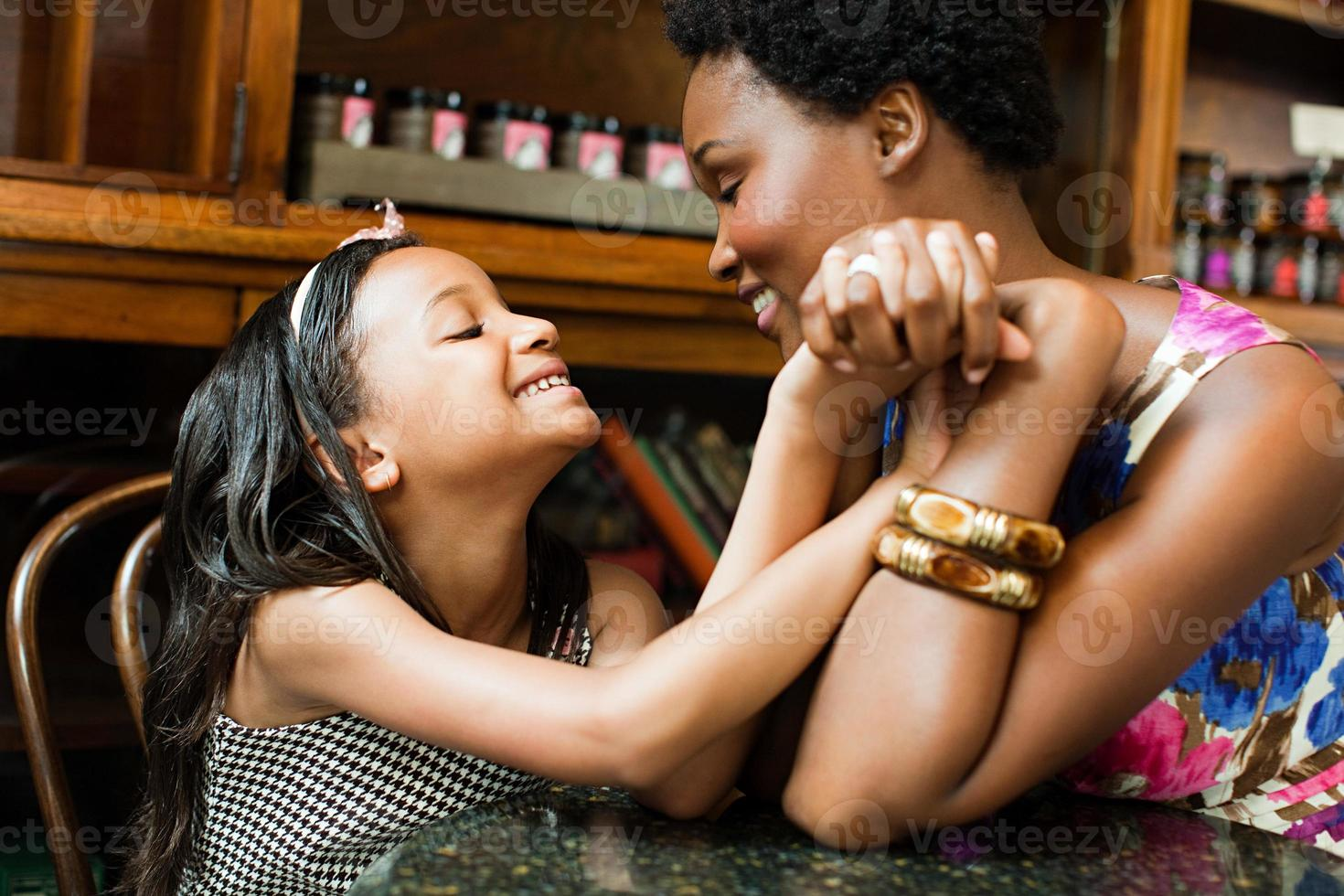 Mother and daughter holding hands in cafe photo