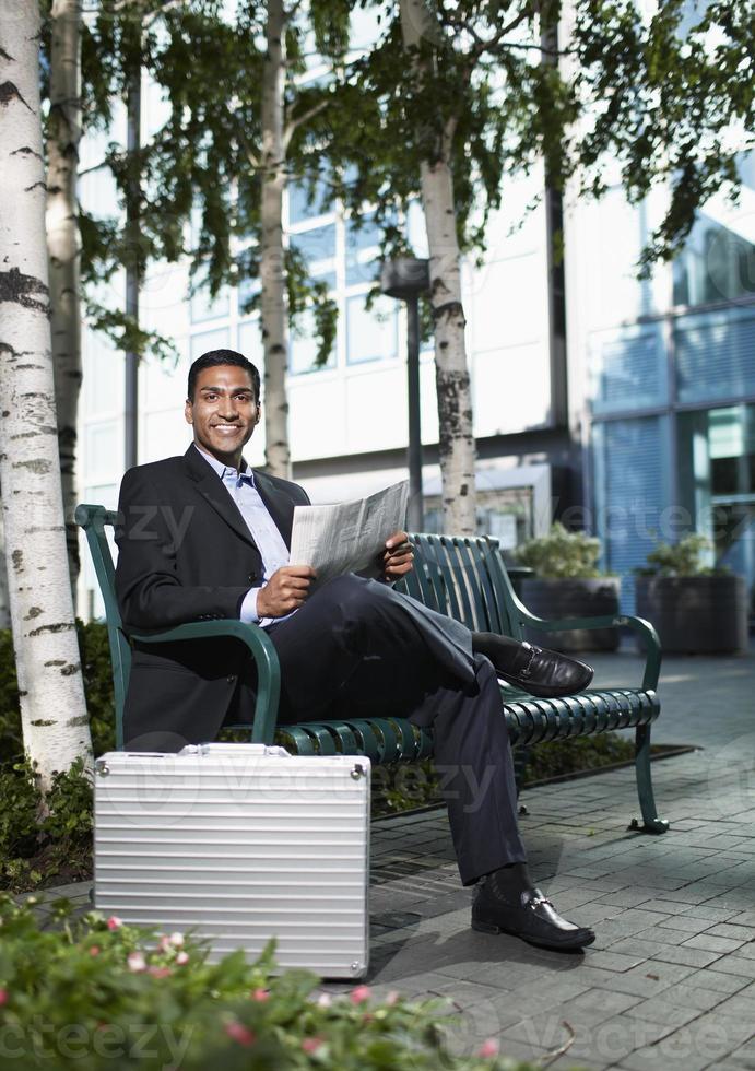 empresario leyendo periódico en banco foto