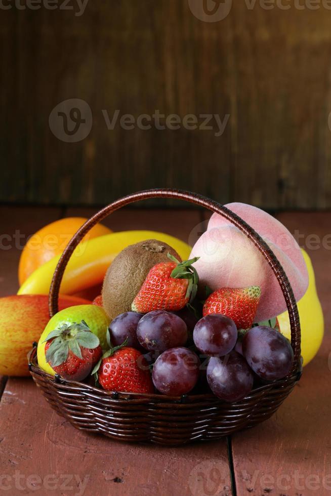 Bodegón cesta de mimbre con fruta en una mesa de madera foto