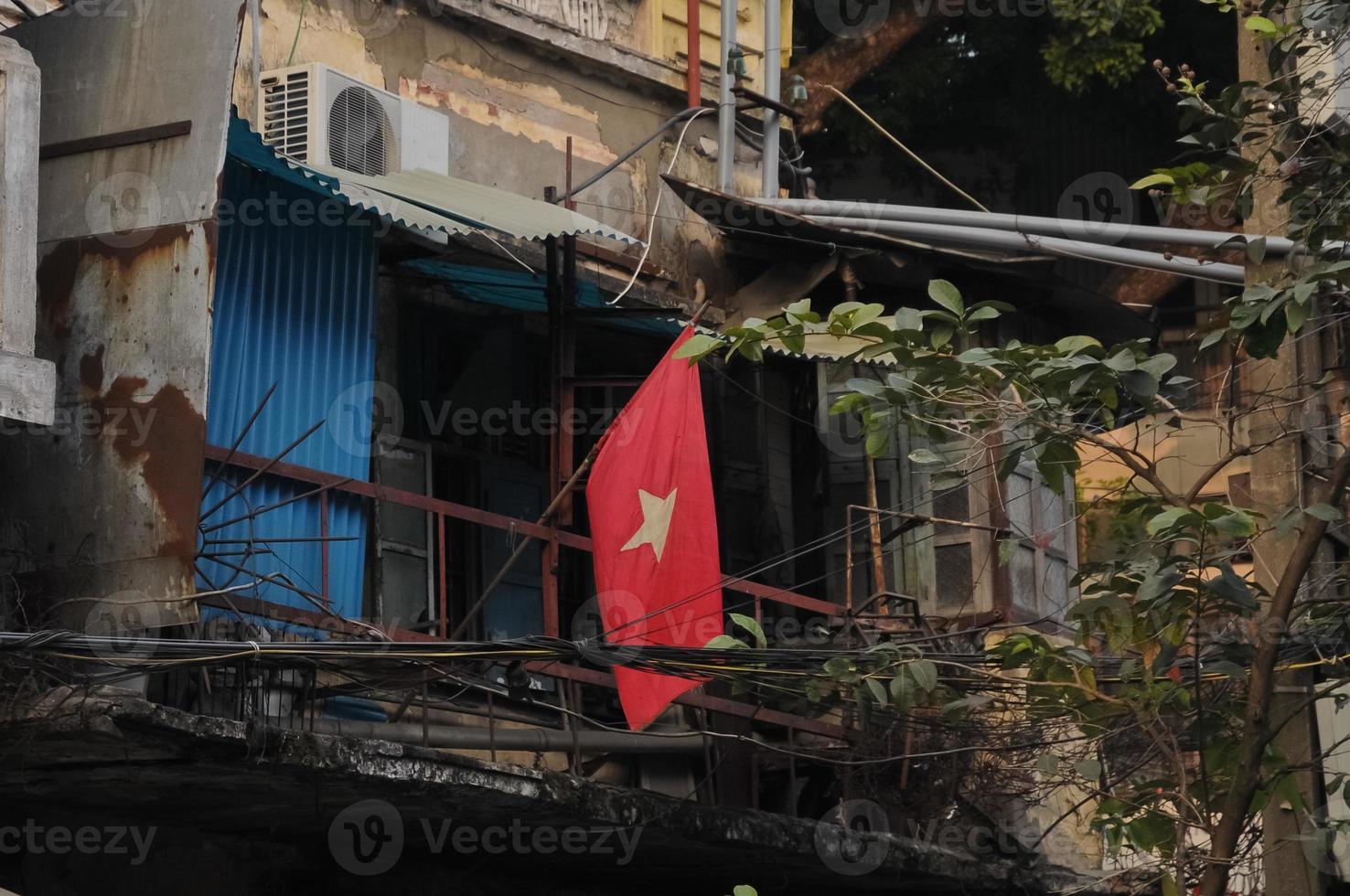 bandera nacional de vietnam y antigua casa de pueblo pobre foto