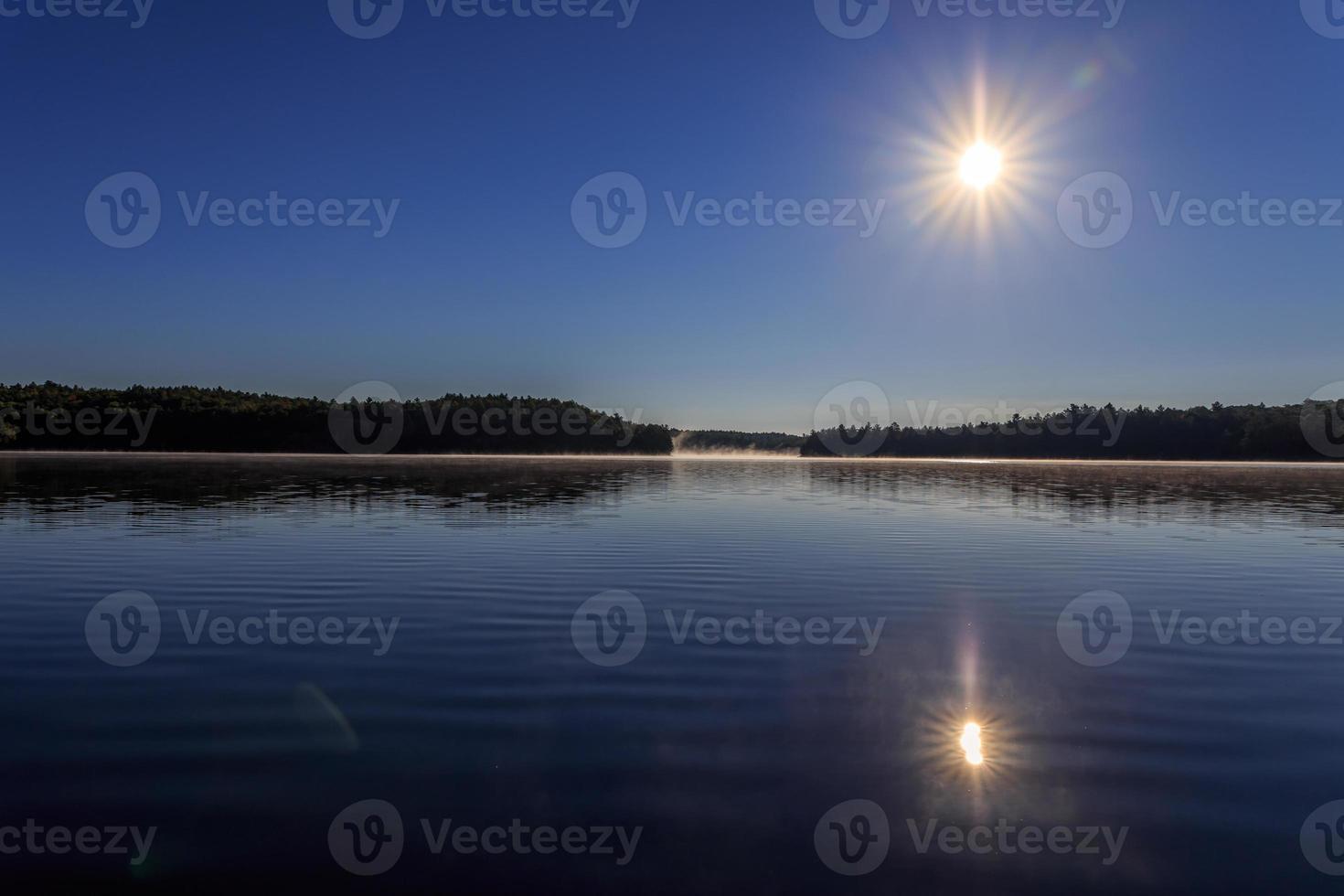 Starburst sun over calm lake photo