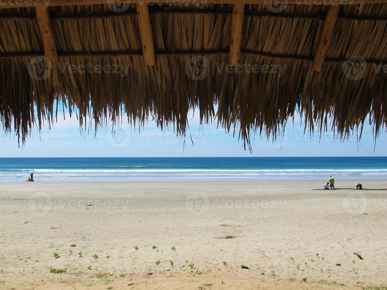 Tranquil beach with palm leaf cabana. photo