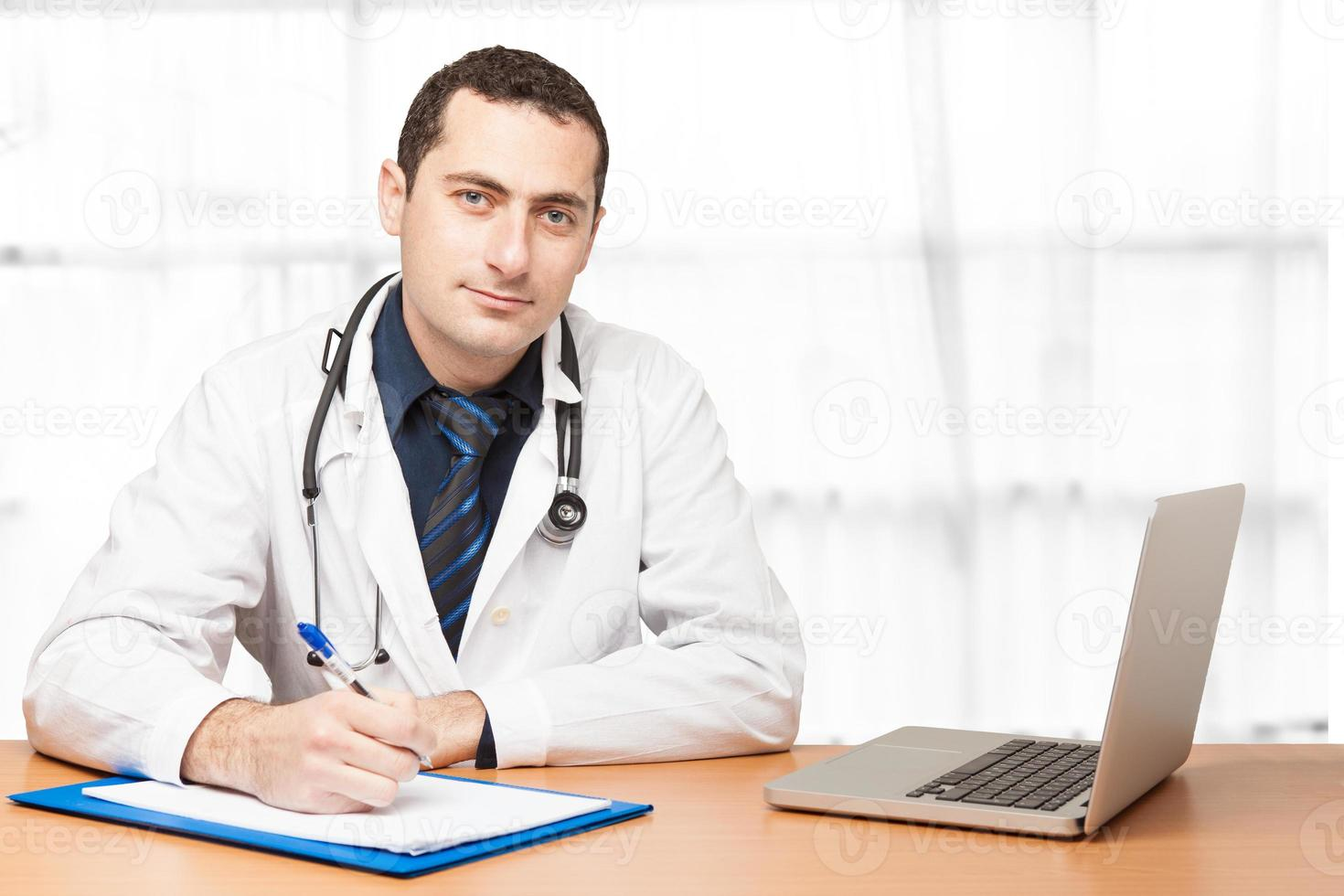Doctor filling out medical document photo