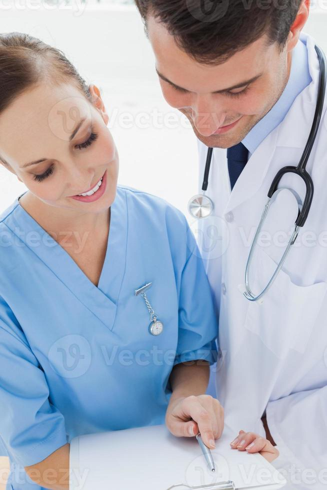 Smiling doctor and surgeon viewing documents together photo