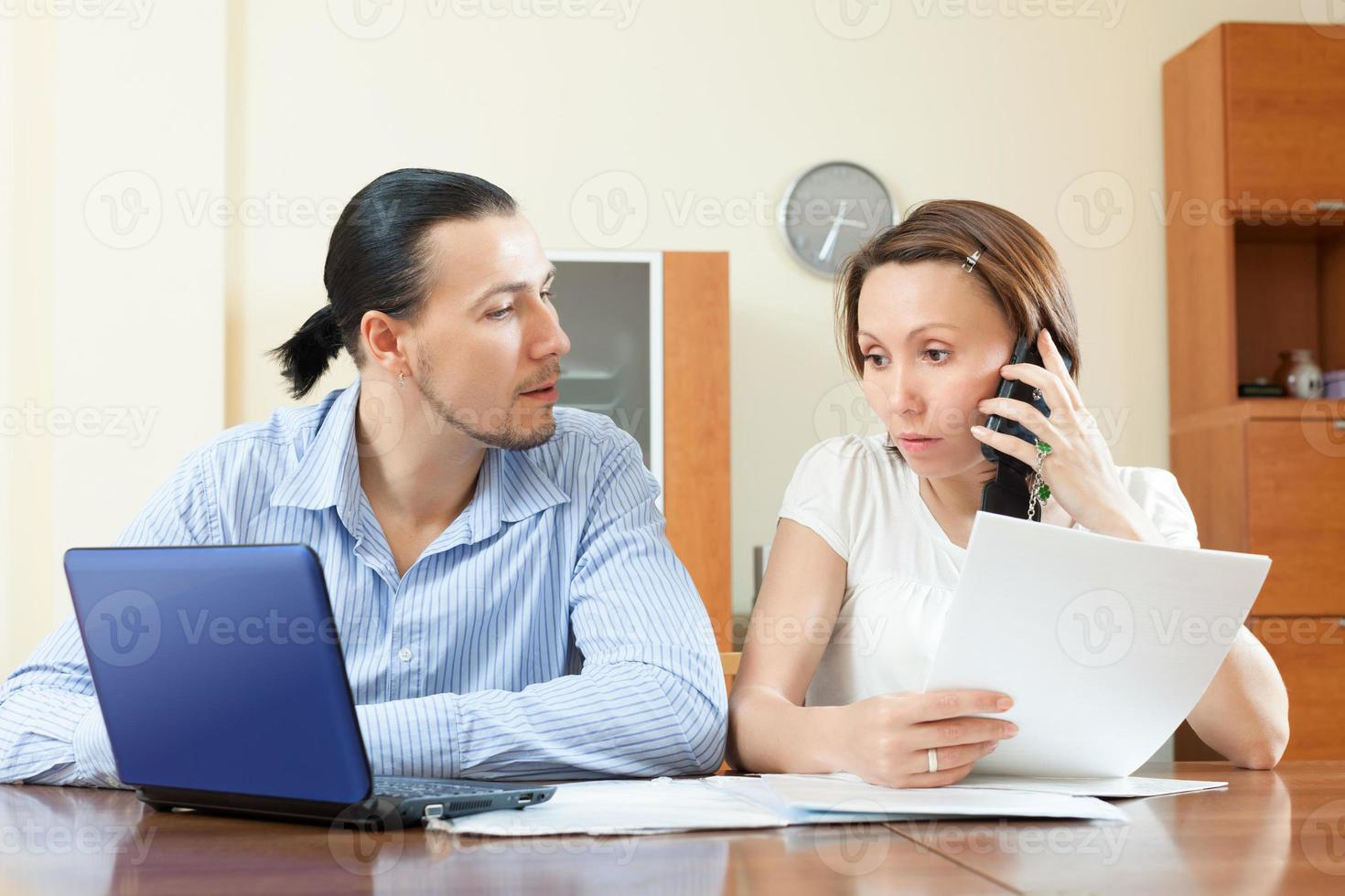 couple calling by mobile about financial documents photo