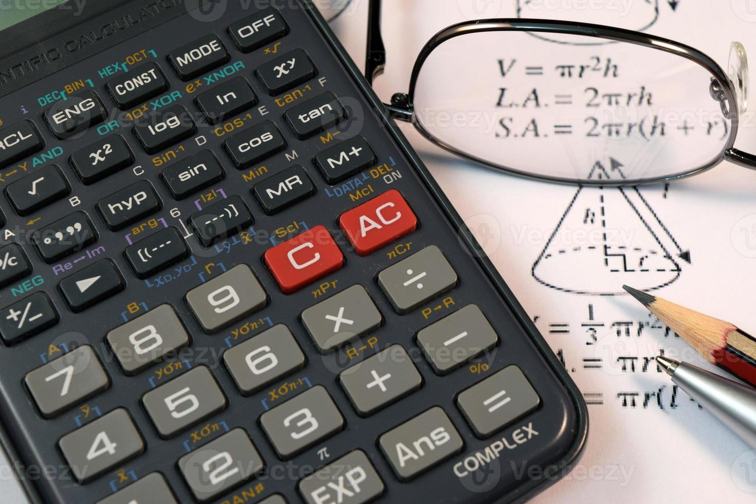 Eye Glasses, pen and pencil over the Formula with calculator photo