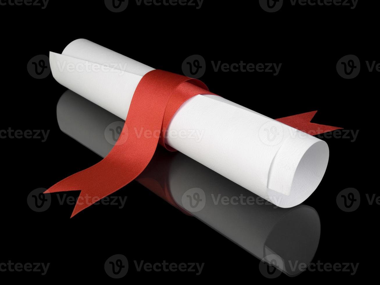 Diploma con cinta roja sobre fondo negro foto