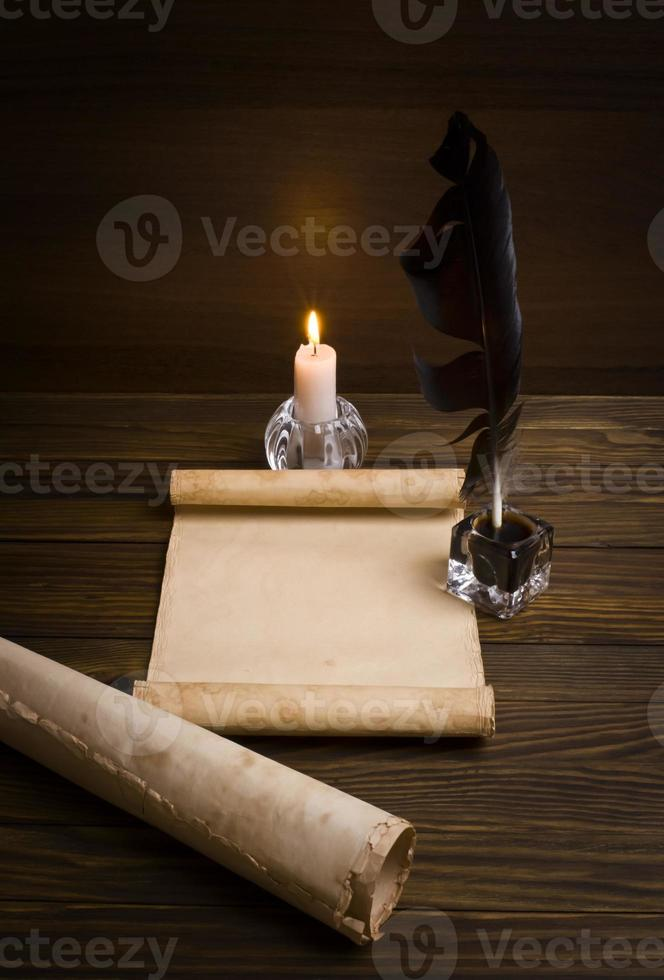 feather, old paper and candle on a wooden background photo