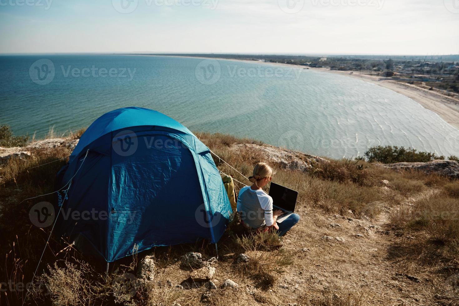 Happy woman sitting near tent with laptop, view of mountains photo