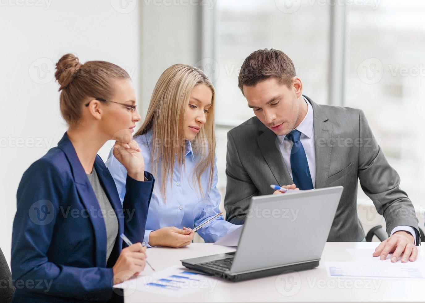 business team with laptop having discussion photo