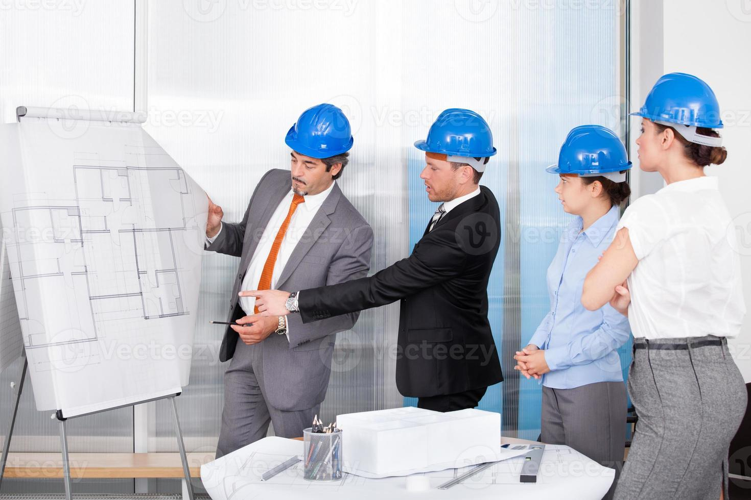 Architects Discussing Plan Drawn On Blueprint At Office photo