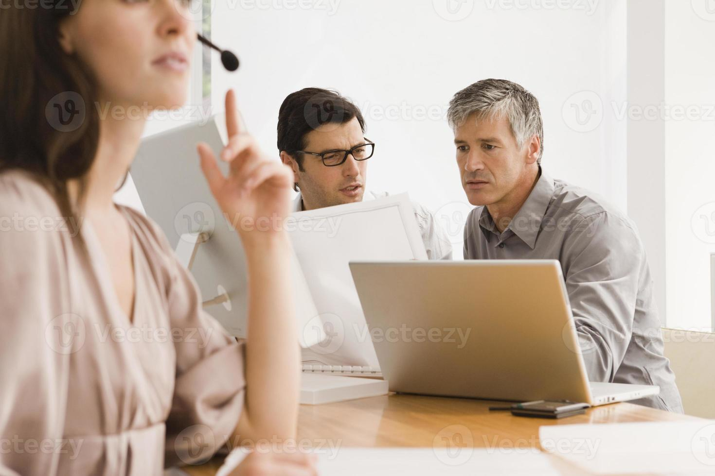 Businesswoman wearing a headset with two businessmen discussing photo