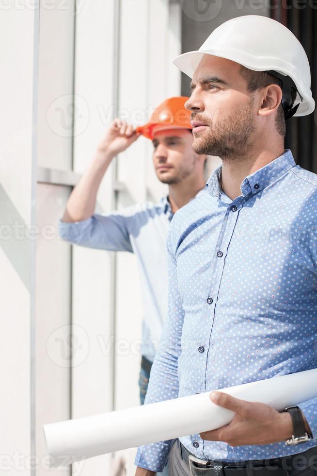 knappe jonge bouwers werken aan een project foto