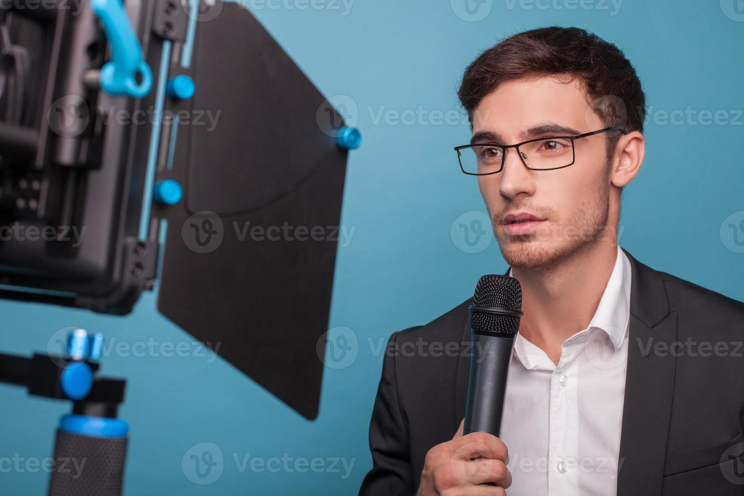 Cheerful young male journalist is reporting with seriousness photo