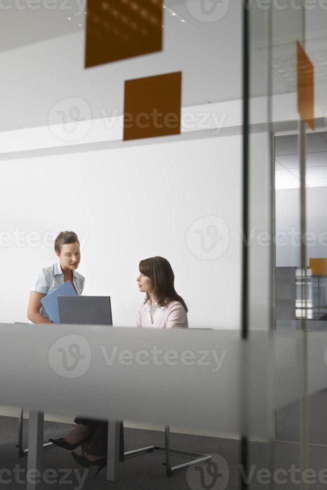 vrouwelijke ondernemers met bestand en laptop met een discussie op kantoor foto