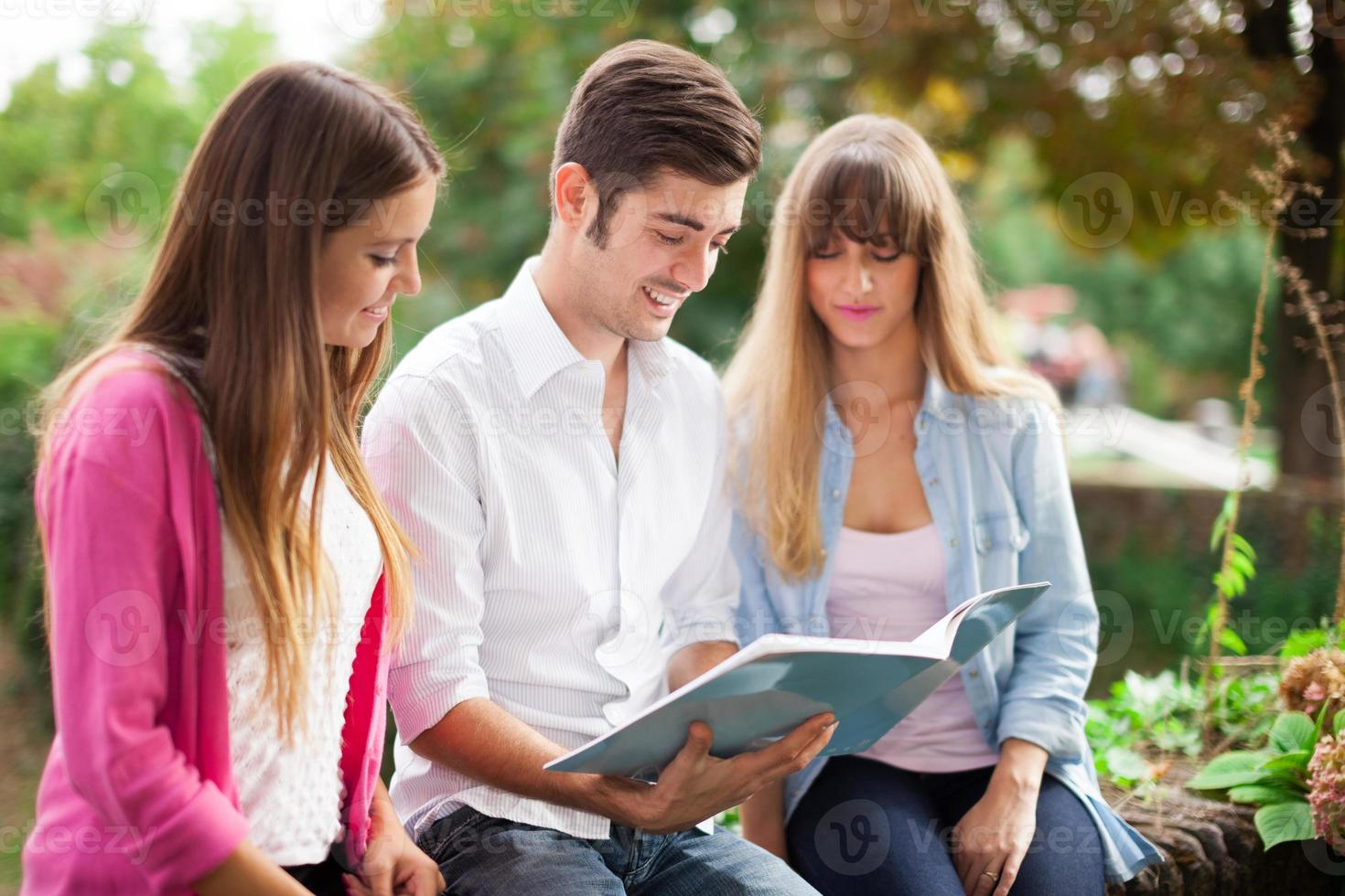 Friends reading a notebook together photo