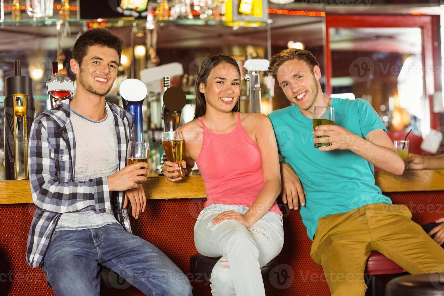 amigos sonrientes bebiendo cerveza juntos foto