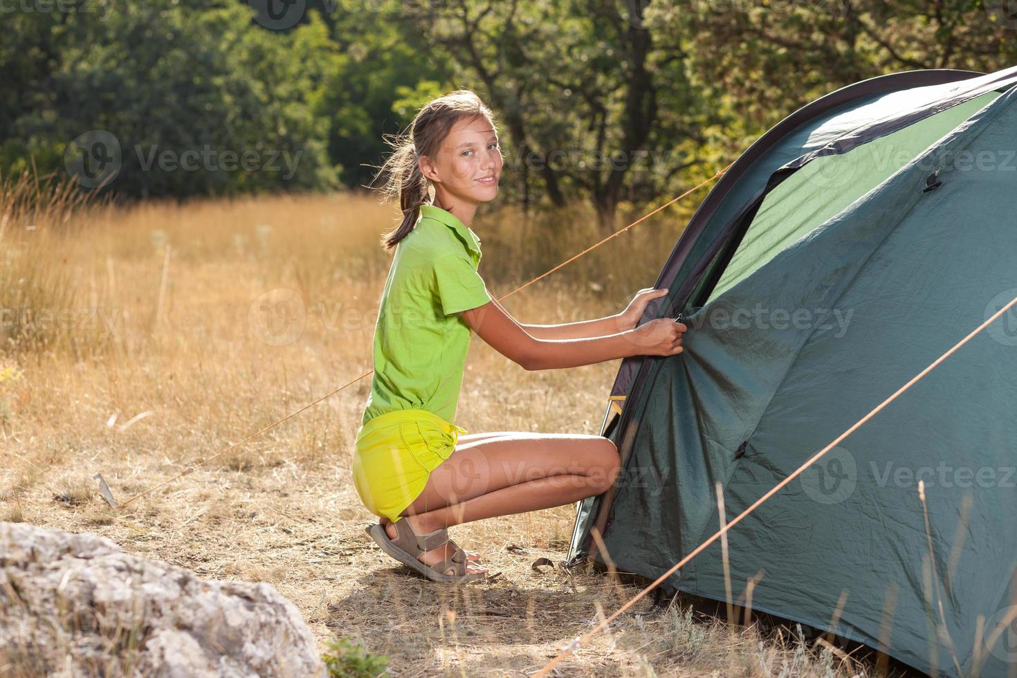 Smiling teenager girl setting a tent photo