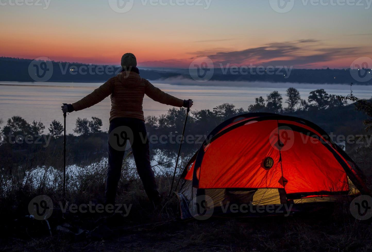 Hiker, tent and sunrise photo