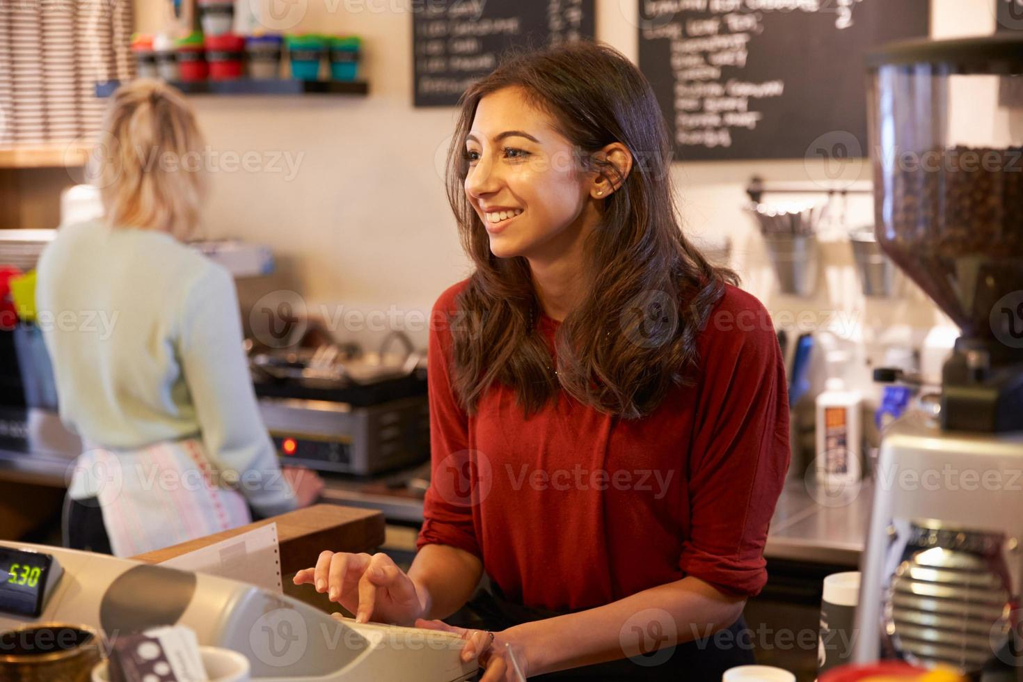 Two female colleagues running coffee shop together photo