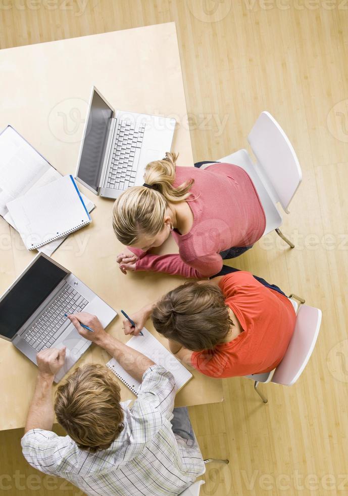 estudiantes que estudian juntos en el aula en computadoras portátiles foto
