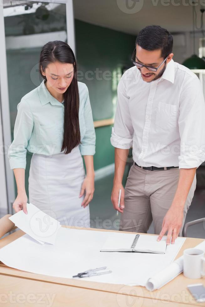 Casual architecture team working together at desk photo