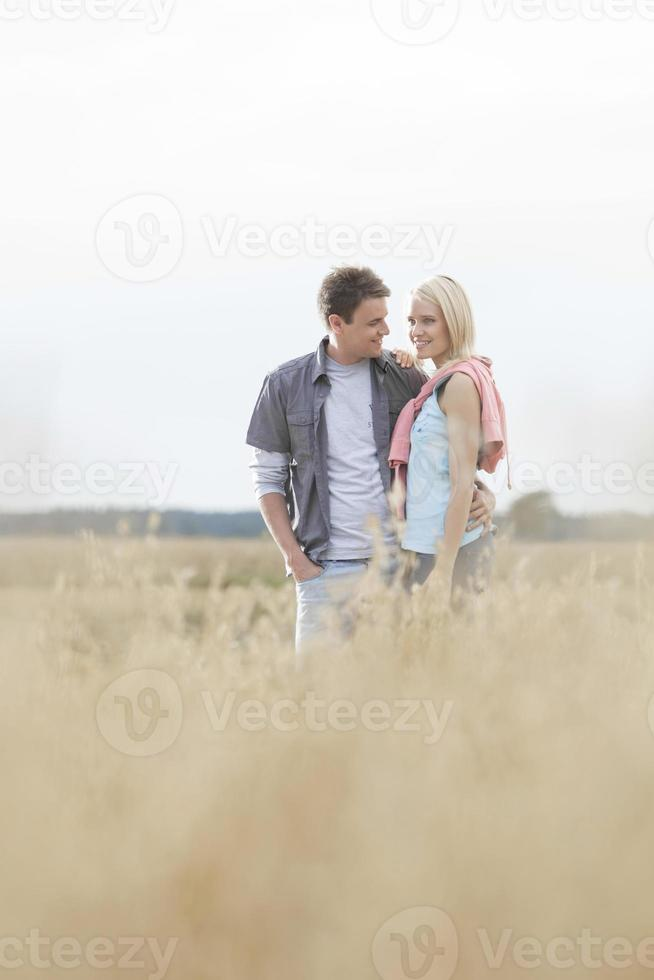 Happy loving young couple standing together at field photo