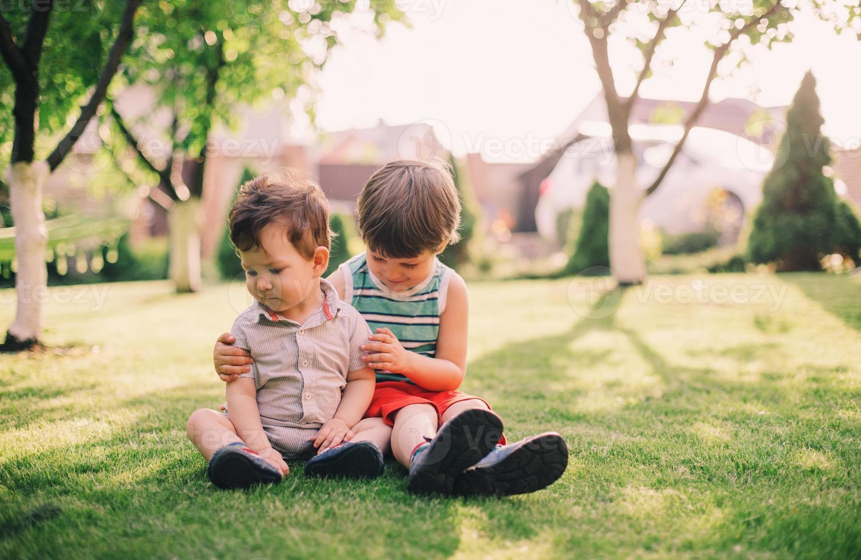 twee broers zitten samen op gras foto
