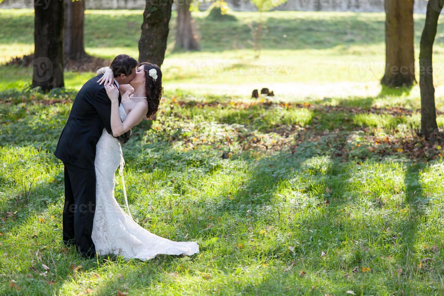 elegante novia y el novio posando juntos al aire libre foto