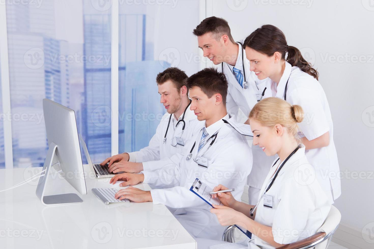 Doctors Working Together On Computer In Hospital photo