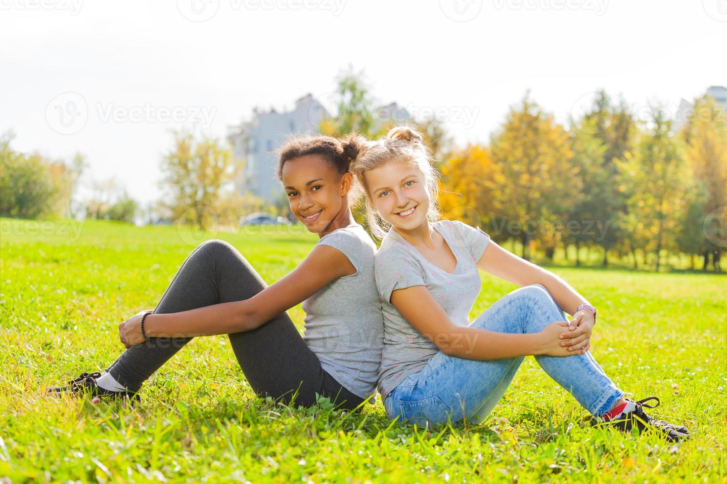 African and blond girl sitting together on grass photo