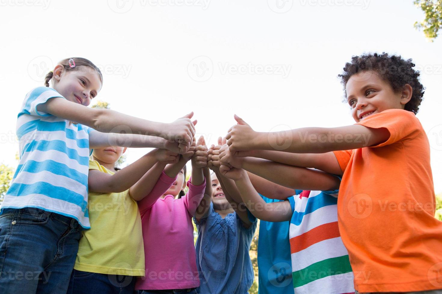 Little children putting thumbs up together photo