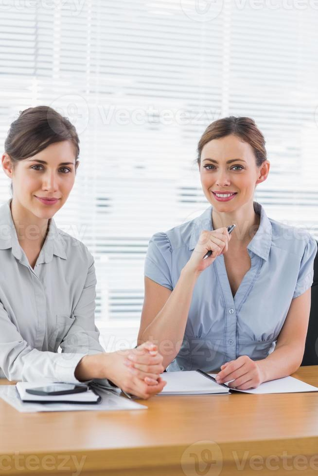 Smiling businesswomen working together and looking at camera photo