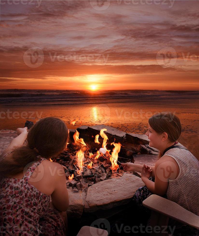 Girls toasting marshmallows outdoors. photo