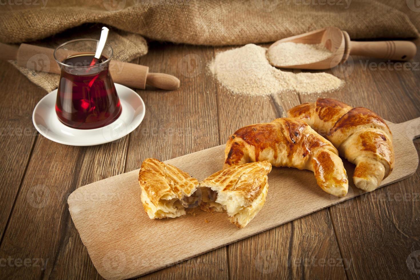 Typical turkish cheese pogaca with wood plate and black tea photo