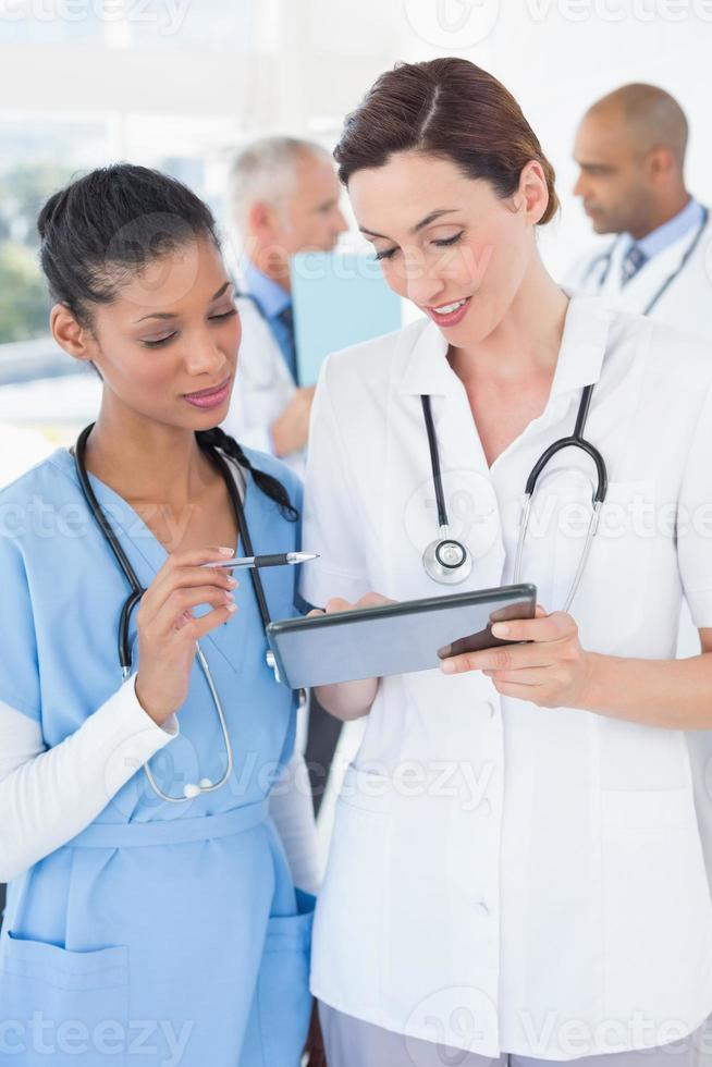 Beautiful female doctors working together with tablet photo