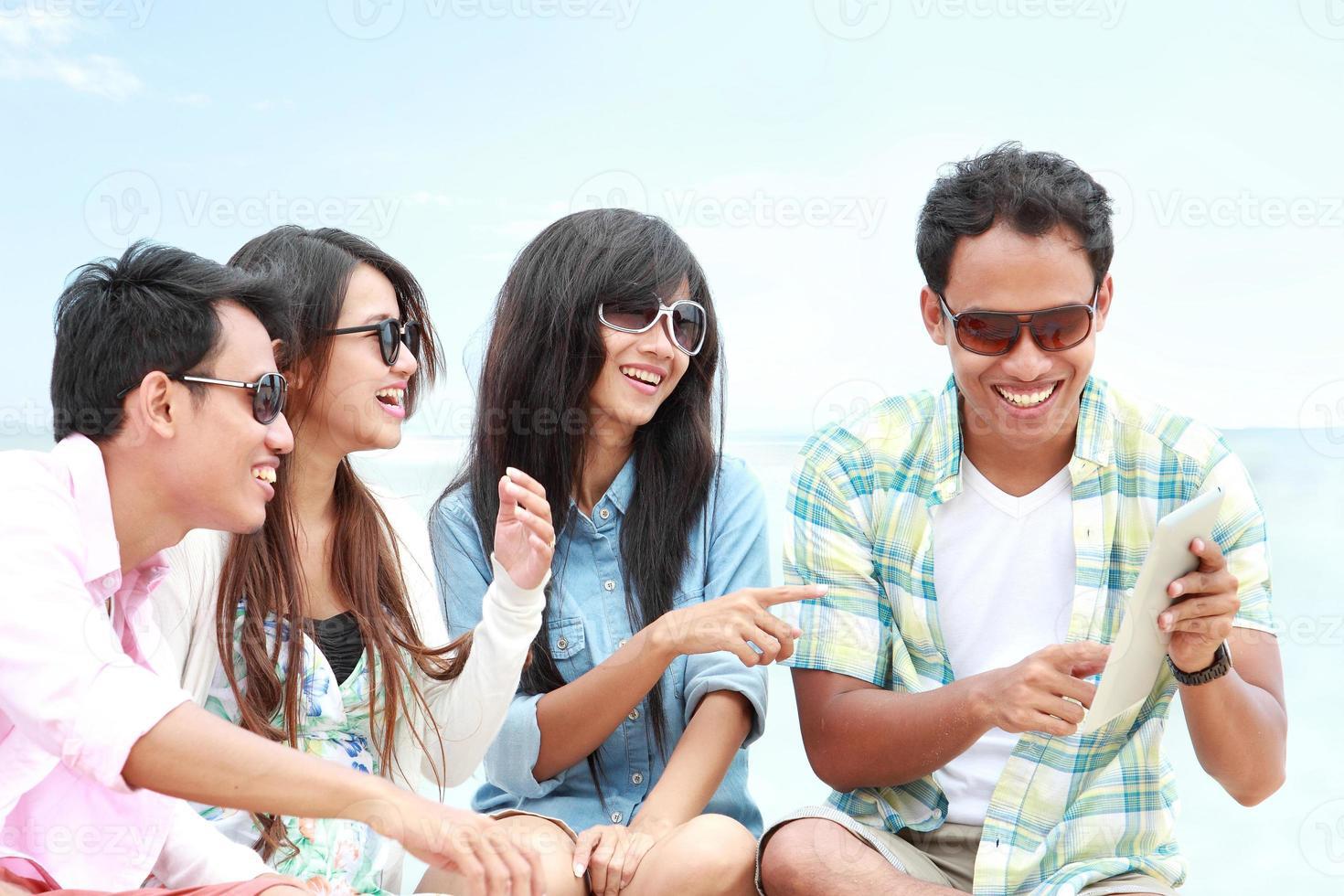 Grupo de amigos disfrutando de vacaciones en la playa junto con Tablet PC foto