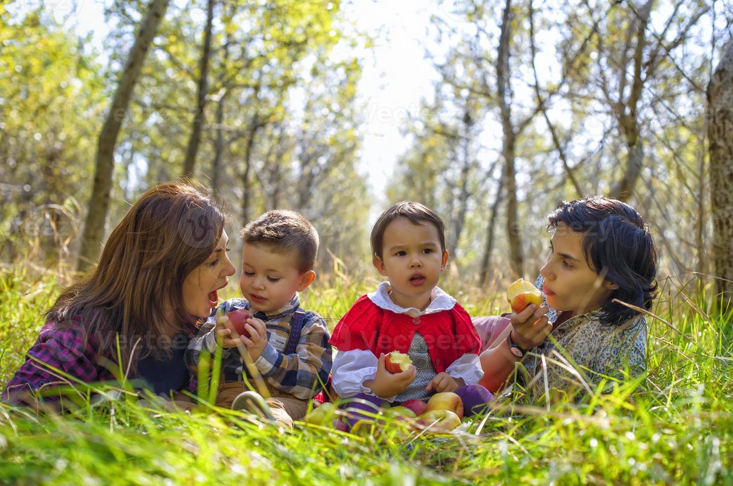 dos madres con sus hijos comiendo manzanas en el bosque foto