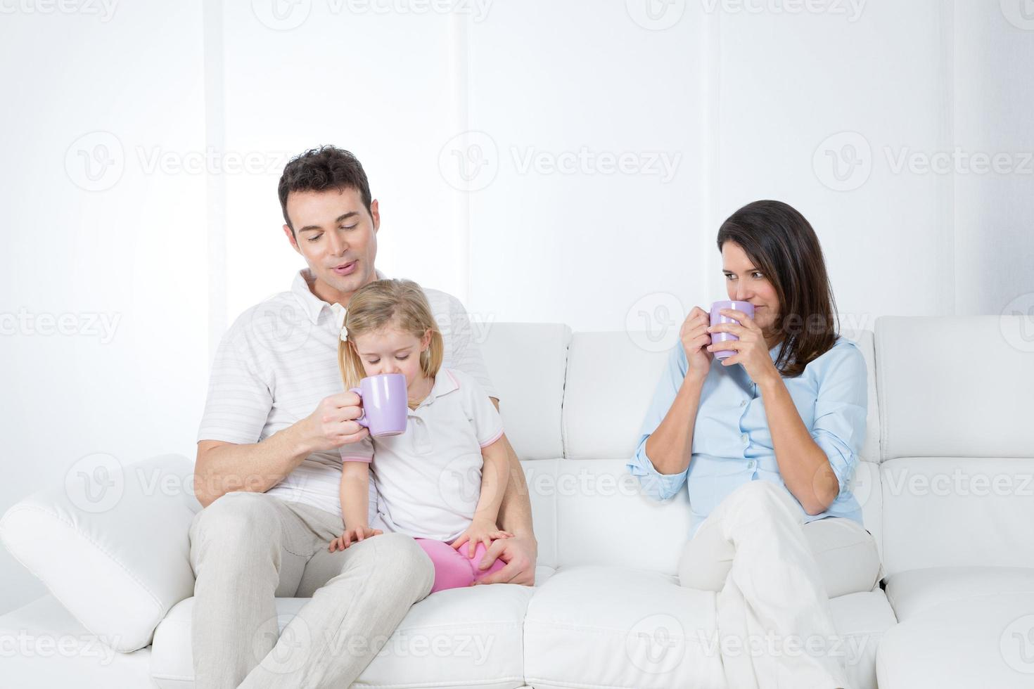 family having breakfast on sofa photo