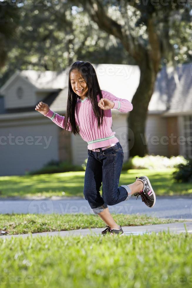 niño asiático jugando rayuela foto