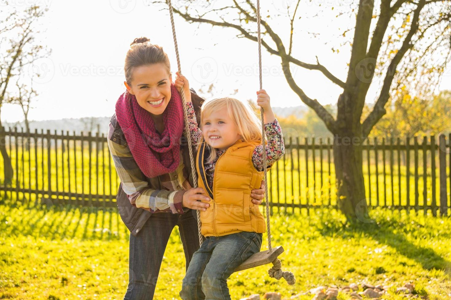 feliz madre balanceándose niño al aire libre foto