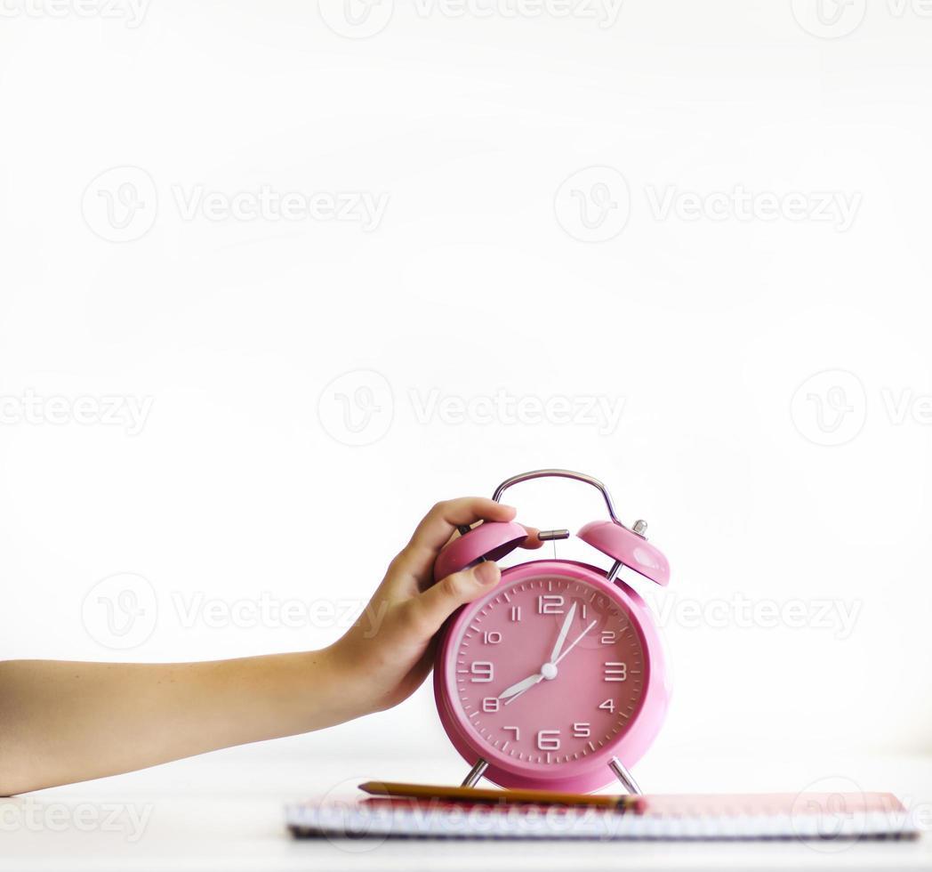 Child turning off loud ringing alarm clock photo