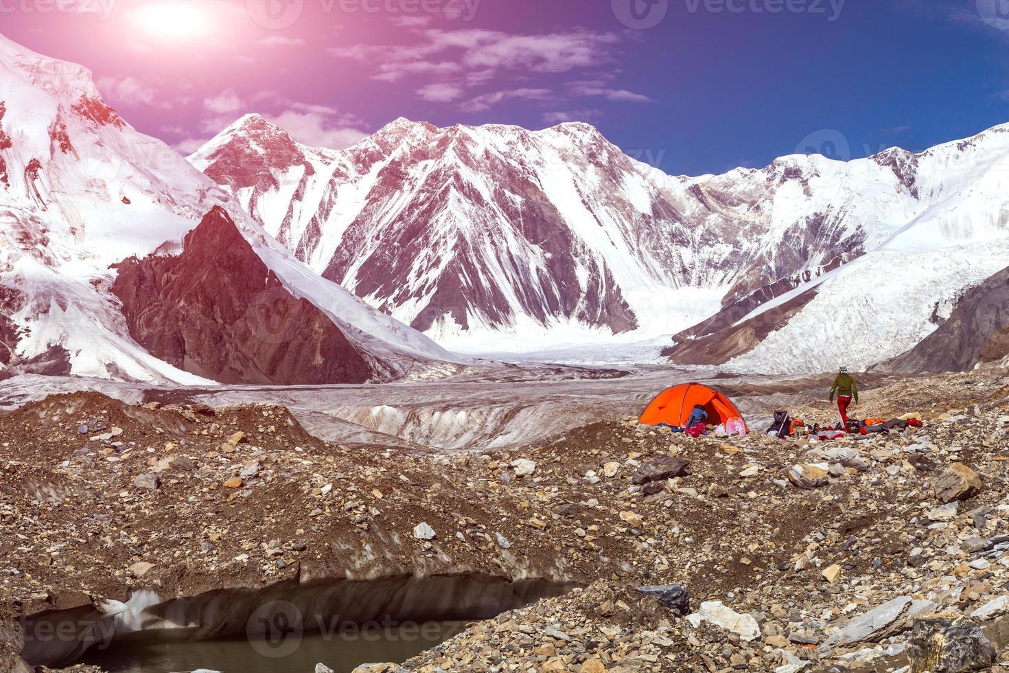 Camping en la morrena del glaciar y el sol nevado con vistas a la montaña foto
