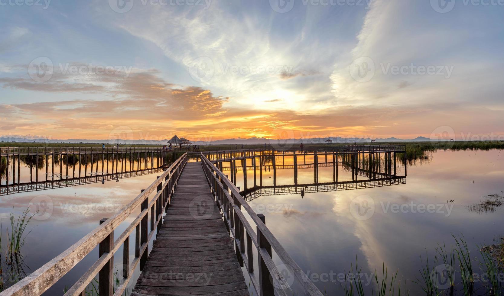 Puente de madera en el lago de loto en la hora del atardecer foto