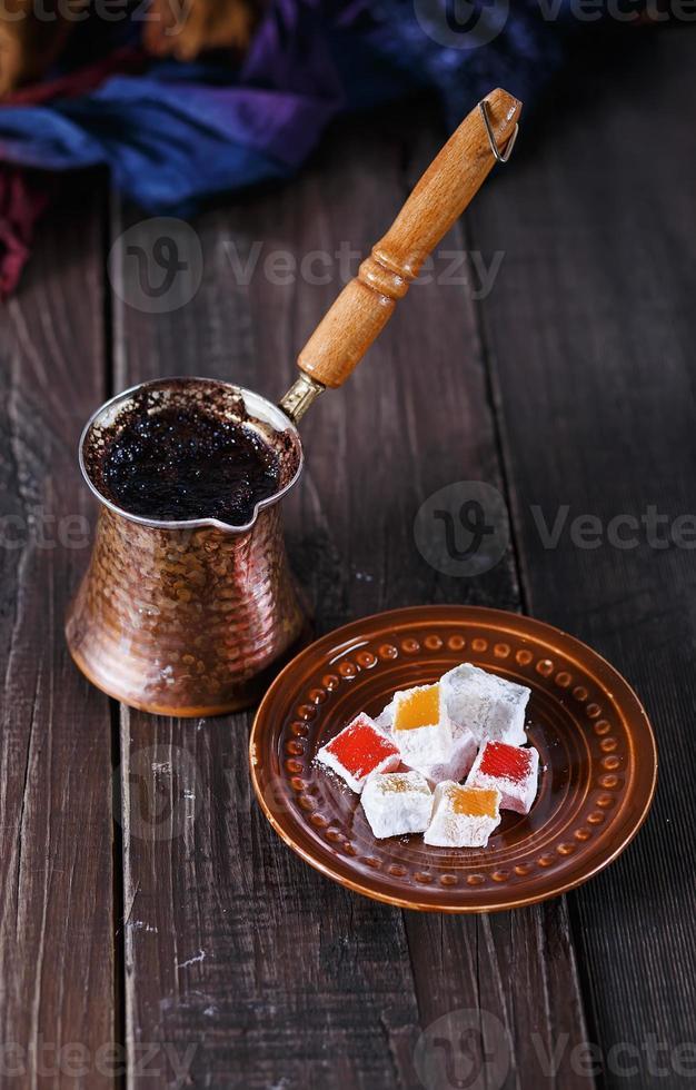 Turkish coffee and Turkish Delight over dark wooden background photo