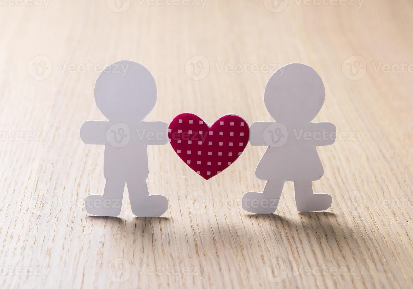 Silhouettes of men, women and heart cut out aper photo