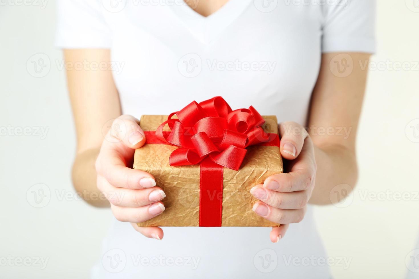 manos femeninas con caja de regalo foto